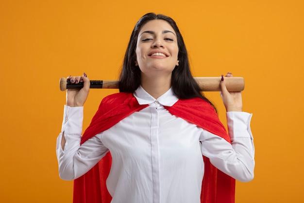 Sorridente giovane superdonna tenendo la mazza da baseball dietro il collo guardando la parte anteriore isolata sulla parete arancione