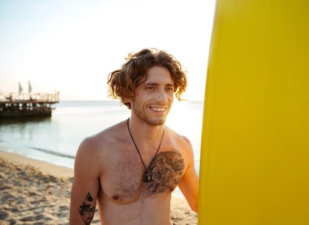 Улыбающийся молодой серфер держит доску для серфинга, стоя на пляже на закате