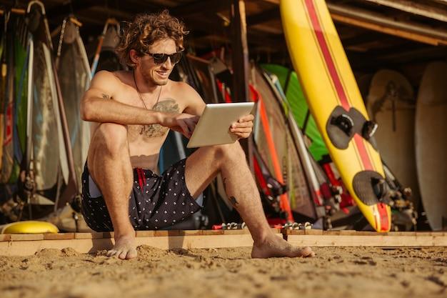 해변에 앉아있는 동안 태블릿을 사용하여 웃는 젊은 서퍼 남자