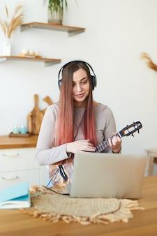 헤드폰으로 웃는 젊은 교사는 학생들과 원격으로 통신합니다. 한 학생이 노트북을 사용하여 온라인 강의를 시청합니다.