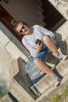 Smiling young teen girl sitting on the steps, listening a music