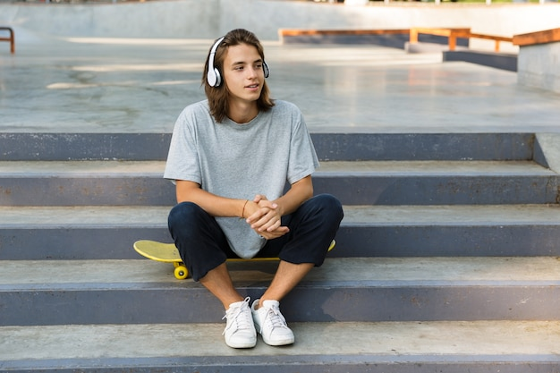 Smiling young teenage boy spending time at the skate park, listening to music with headphones, sitting on skateboard