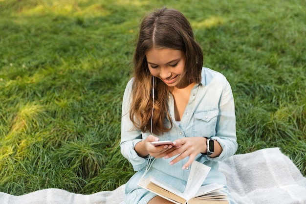 Smiling young teenage girl laying on a grass at the park