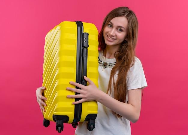 Улыбающаяся молодая путешественница девушка держит чемодан на изолированной розовой стене