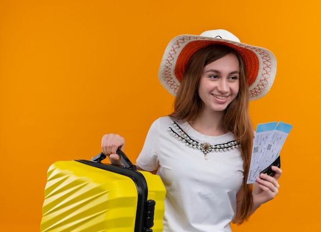 Sorridente ragazza giovane viaggiatore che indossa il cappello che tiene la valigia e biglietti aerei, carta di credito sulla parete arancione isolata
