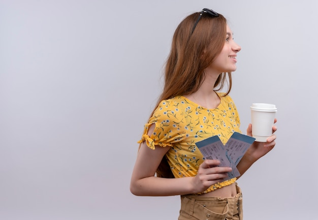 コピースペースのある孤立した白い壁の右側を見て飛行機のチケットを保持している頭にサングラスをかけている若い旅行者の女の子の笑顔