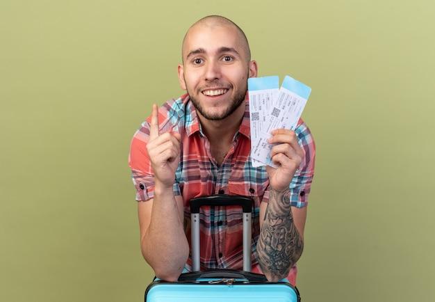 비행기표를 들고 올리브 녹색 벽에 복사 공간이 있는 가방 뒤에 서서 가리키는 웃고 있는 젊은 여행자