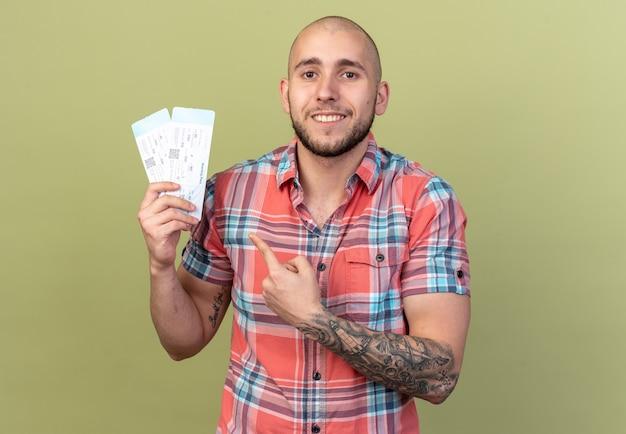 Sorridente giovane viaggiatore uomo che tiene e punta a biglietti aerei isolati su parete verde oliva con spazio di copia