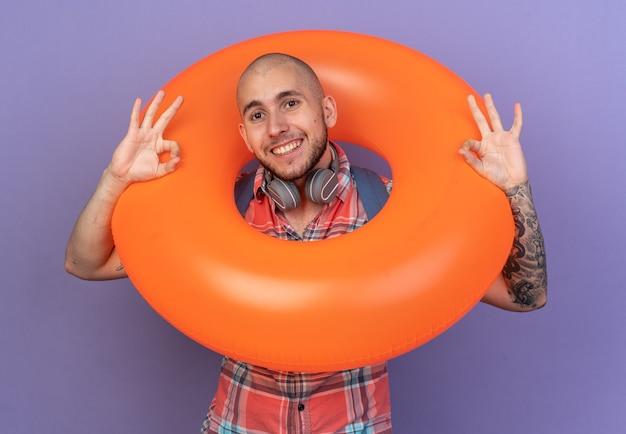 彼の首の周りにヘッドフォンとコピースペースで紫色の壁に分離されたokサインを身振りで示す浮き輪を保持しているバックパックと笑顔の若い旅行者の男