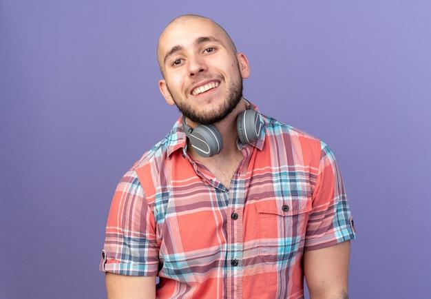 コピースペースと紫色の壁に分離された正面を見て彼の首の周りにヘッドフォンで笑顔の若い旅行者の男
