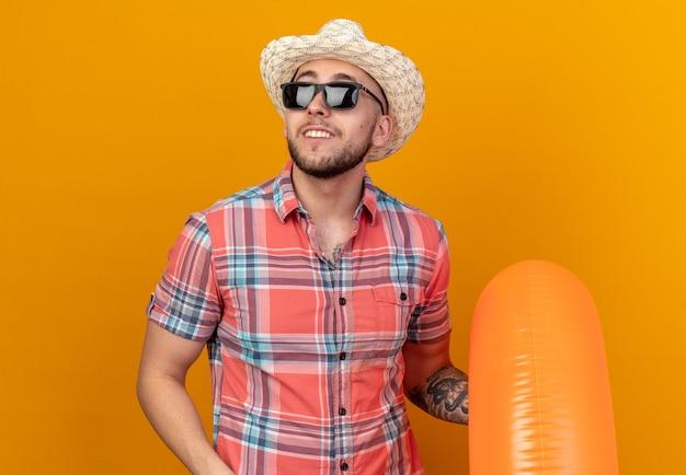 복사 공간이 있는 주황색 벽에 고립된 쪽을 바라보며 수영 반지를 들고 태양 안경에 밀짚 해변 모자를 쓴 웃고 있는 젊은 여행자