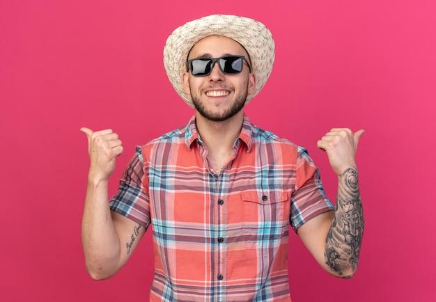 복사 공간이 있는 분홍색 벽에 격리된 측면을 가리키는 태양 안경에 밀짚 해변 모자를 쓴 웃고 있는 젊은 여행자