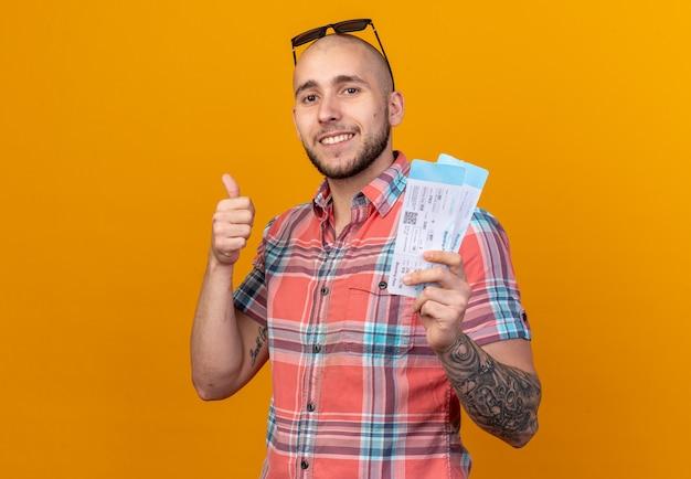 Sorridente giovane viaggiatore con occhiali da sole in possesso di biglietti aerei e pollice in alto isolato sulla parete arancione con spazio di copia
