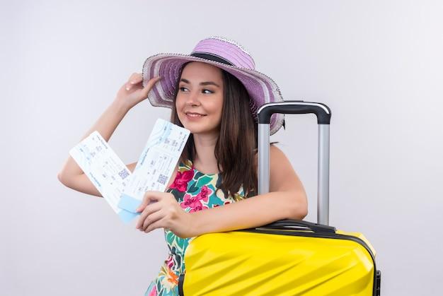 分離の白い壁に飛行機のチケットとスーツケースを保持している若い旅行者の女性の笑顔