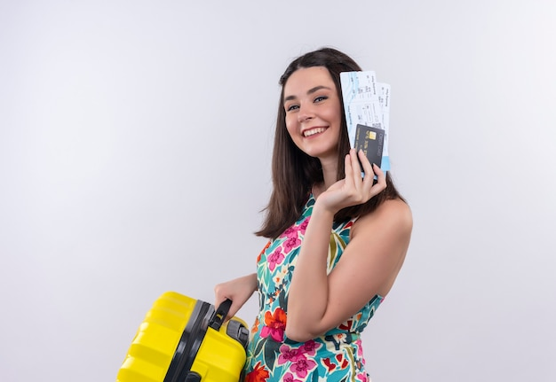 Smiling young traveler woman holding airplane tickets and suitcase on isolated white wall