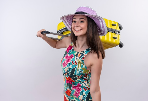 Smiling young traveler woman holding suitcase on isolated white wall
