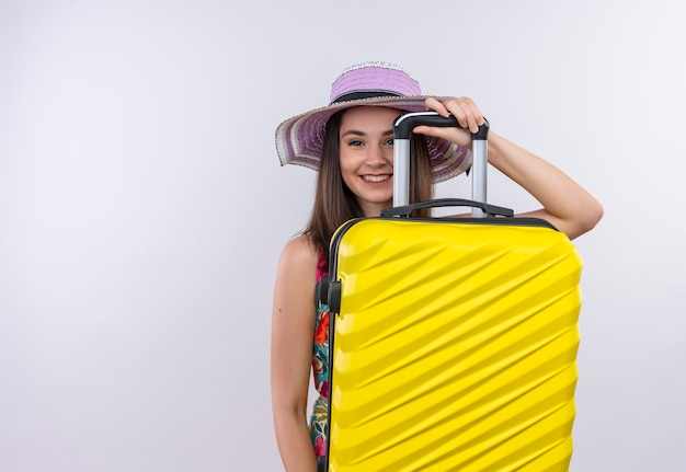 Donna sorridente del giovane viaggiatore che tiene la valigia sulla parete bianca isolata