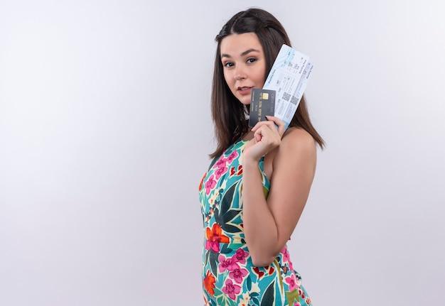 白い壁の女性のチケットとカードを保持している多色のドレスを着ている若い旅行者の女性の笑顔