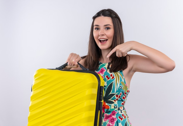 Smiling young traveler woman wearing multicolor dress holding a mobile bag and points to the bag on white wall