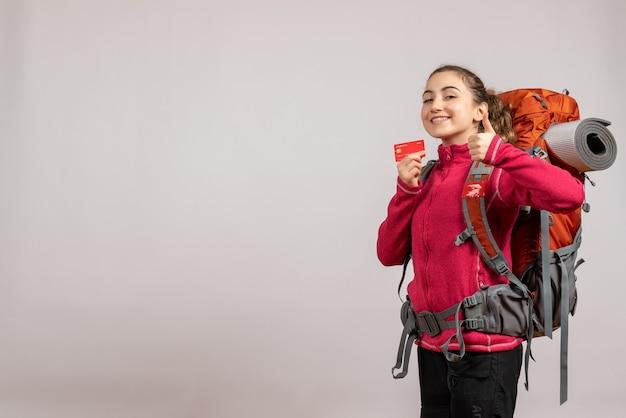 サインアップの親指を作るカードを保持している大きなバックパックを持つ若い旅行者の笑顔