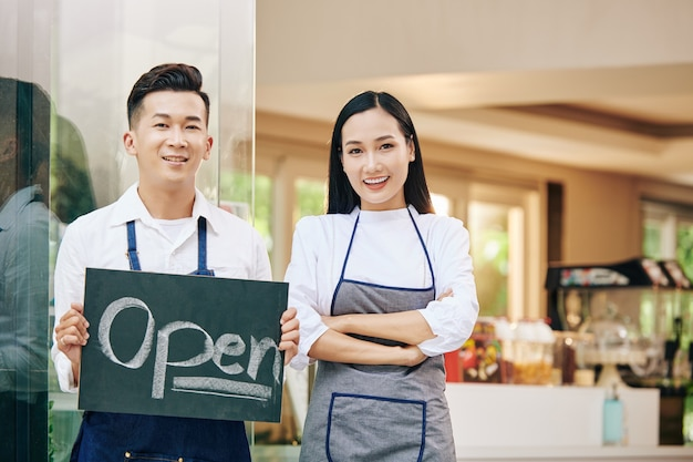 Smiling young vietnamese cafe owners with open sign standing at cafe entrance and welcoming customers inside