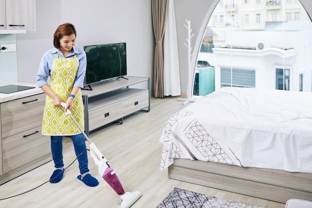 彼女のアパートのスタジオで若いベトナム人主婦掃除機の床を笑顔