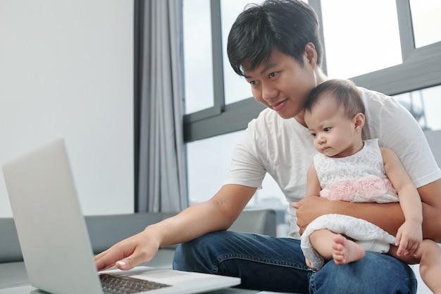 Улыбающийся молодой вьетнамский мужчина работает на ноутбуке дома и тестирует новую компьютерную программу с маленьким задротом, сидящим у него на коленях