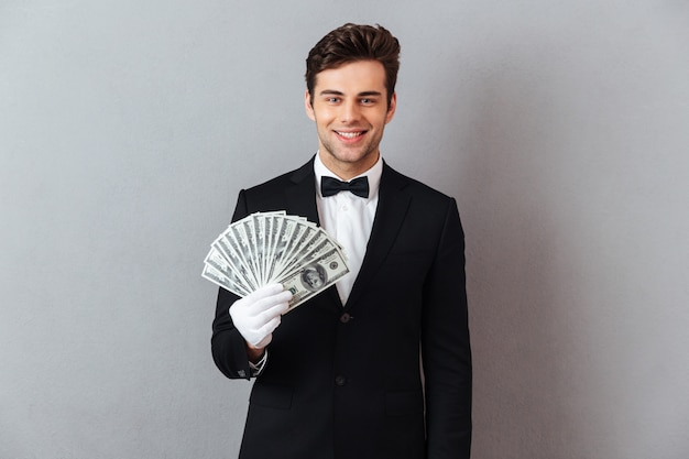 Smiling young waiter holding money.