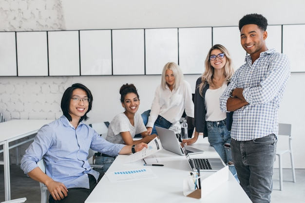 ノートパソコンを載せたテーブルの周りでポーズをとる若いウェブ開発者の笑顔。大学で友達と時間を過ごす黒髪のアジアの学生の屋内肖像画。