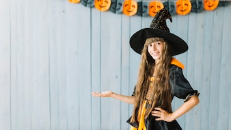 Smiling young witch showing Halloween costume