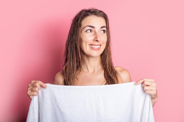 Улыбающаяся молодая женщина после душа укрывается полотенцем на розовом фоне.