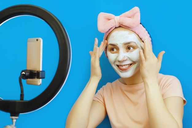 Smiling young woman applies cosmetic mask of cream to her face and broadcasts online on her smartphone in social networks with her followers
