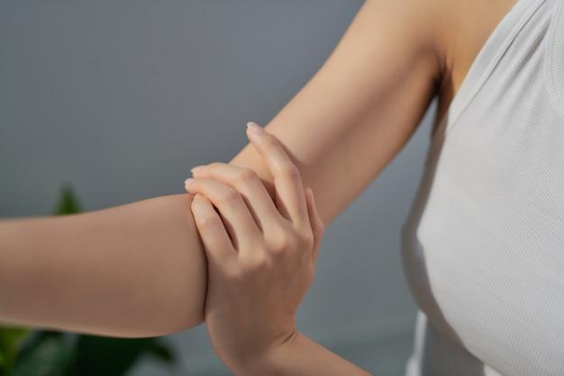 Улыбающаяся молодая женщина наносит крем на руки