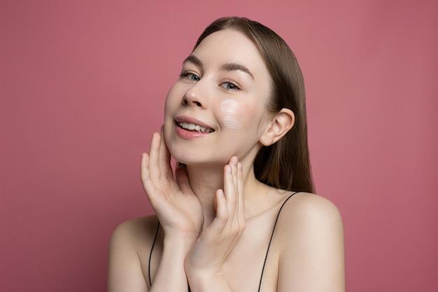 保湿クリーム、ピンクの背景に指で顔にローションを適用する笑顔の若い女性健康的な治療と美容製品。顔を掃除する女の子。美容ルーチン、スキンケアの概念