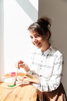 パレットを保持している笑顔の若い女性アーティスト