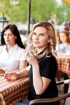 Улыбается молодая женщина в кафе, пить белое вино. концепция общения и дружбы.