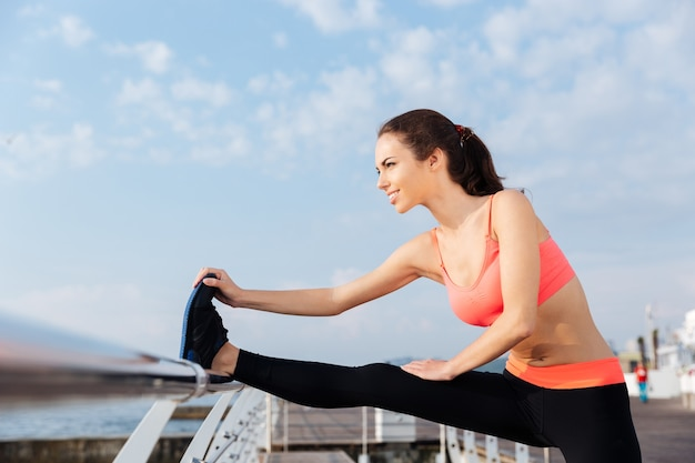 Smiling young woman athlete doing stretching exercises on pier in the morning