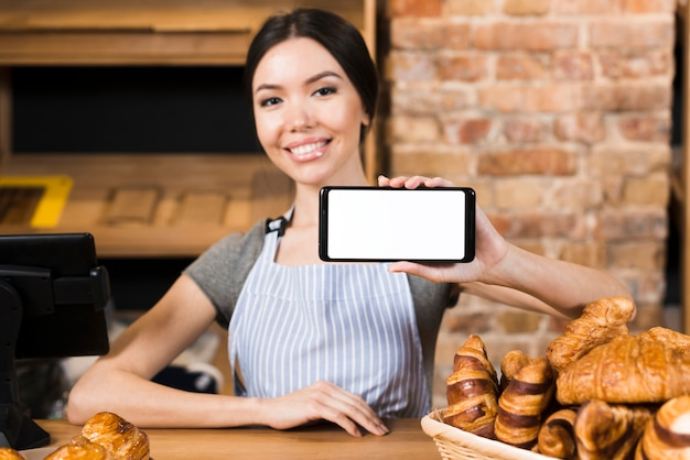 Smiling young woman at the bakery counter showing his mobile phone