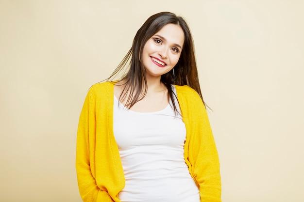 若い女性の笑顔。白いズボンと黄色いセーターの美しいブルネット。