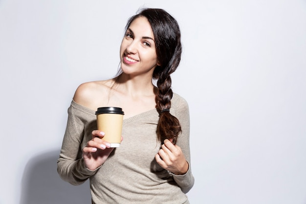 Smiling young woman. beautiful brunette with a cup of coffee in her hand. white background.
