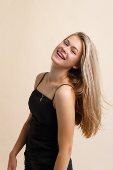 A smiling young woman on a beige background