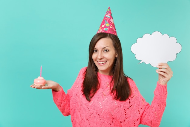 Smiling young woman in birthday hat hold in hand cake with candle empty blank say cloud speech bubble for promotional content isolated on blue background. people lifestyle concept. mock up copy space.