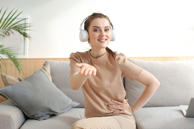 웃고 있는 젊은 여성 블로거 인플루언서가 집에서 일하고 있습니다. 웹 카메라에서 말하는 소녀, 화상 채팅 또는 회의 통화, 여성 녹화 vlog.