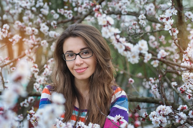 Smiling young woman in the blossoming spring garden