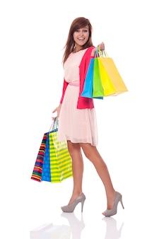 Giovane donna sorridente che trasporta molte borse della spesa
