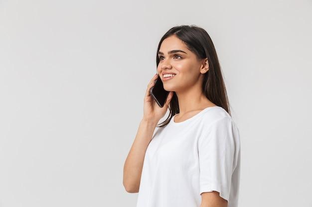 Улыбающаяся молодая женщина, одетая в повседневную одежду, стоя изолирована на белом, разговаривает по мобильному телефону