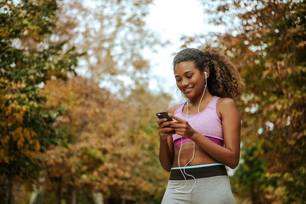 Smiling young woman checking her smartphone while resting after workout.