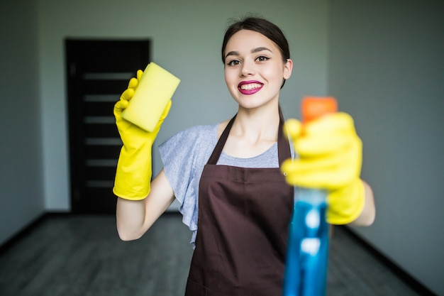 Smiling young woman clean the window with rag