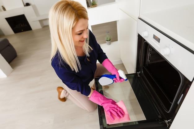 笑顔の若い女性は彼の家で現代のストーブクリーナーを掃除します