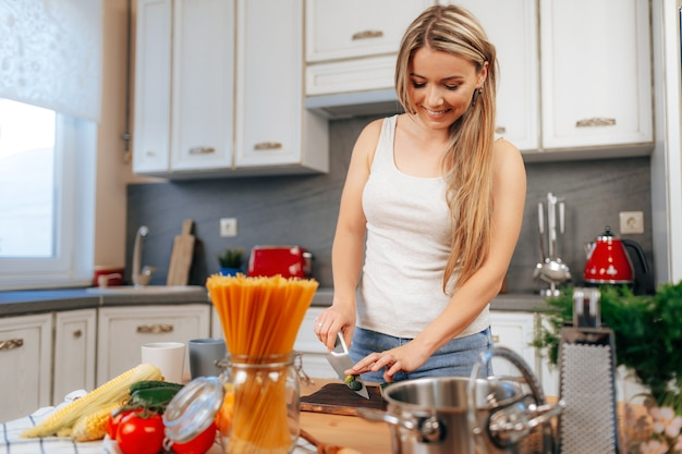 Smiling young woman cooking something at her kitchen at home